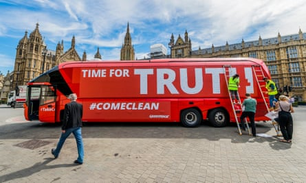 John Sauven, executive director of Greenpeace UK, strides past the Leave campaign's battle bus that was re-branded and parked outside Parliament