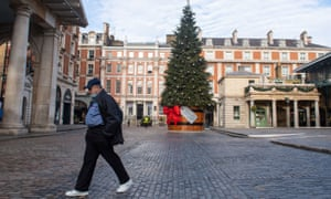 A man with a face mask in Covent Garden, London, where a Christmas tree is up, but the lockdown continues.