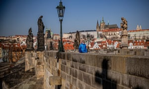 A man wearing a protective face mask walks on Charles Bridge in Prague