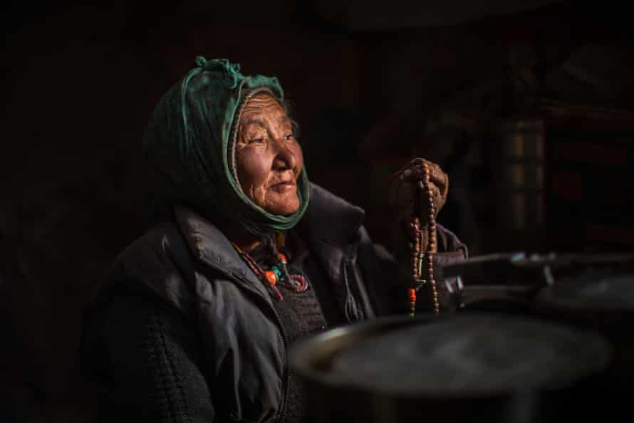 A village elder watches the snow falling out of the window, praying that it will not disrupt the migration.