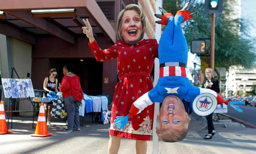 A man wears a mask depicting Hillary Clinton while holding a doll depicting Republican presidential nominee Donald Trump in Phoenix, Arizona.