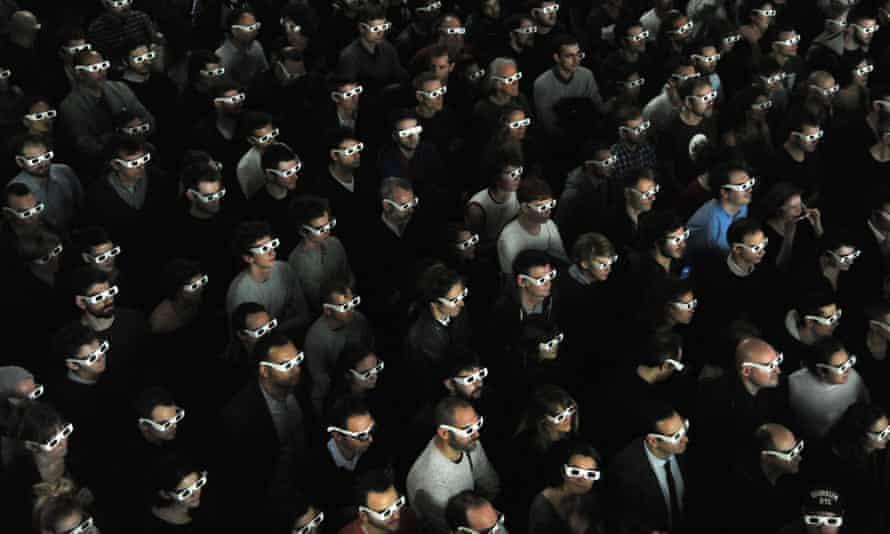 Spectators wearing 3D glasses watch a live concert by Kraftwerk