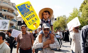 Iranian boy on his father's shoulders at protest in Tehran