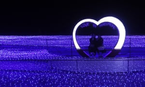 A couple takes pictures in a heart shape light installation during a light festival in Busan, South Korea