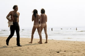 Naked festivalgoers enjoy the beach, Isle of Wight
