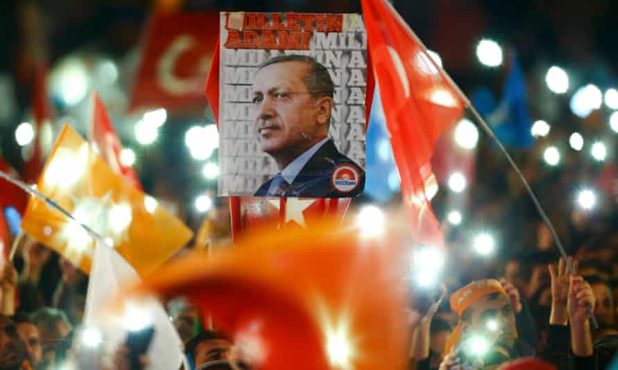 People wave flags and hold a portrait of Recep Tayyip Erdoğan