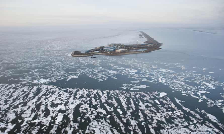 An oil well drilling platform on a man-made island and surrounded by broken sea ice.