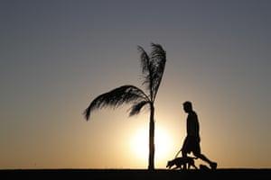 Asuncion, Paraguay. A man walks his dog as the sun sets