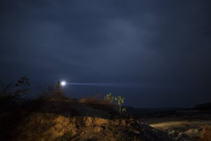A man holding a flashlight searches for a cell signal atop a small hill