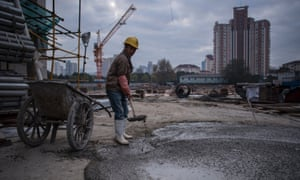 A man fills a cart with cement at a construction site for a residential skyscraper in Shanghai.