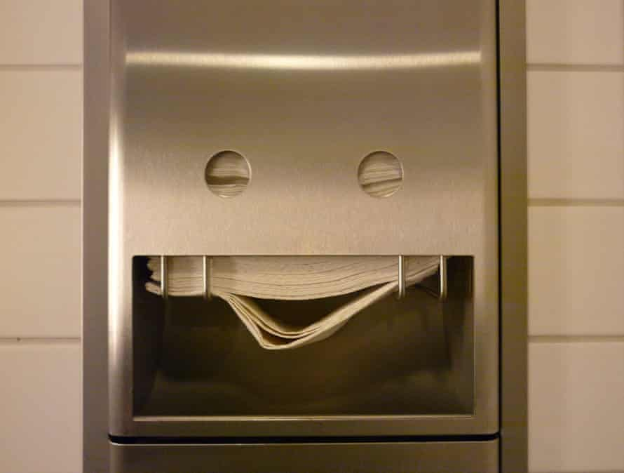 A towel dispenser in a public bathroom that appears to be smiling