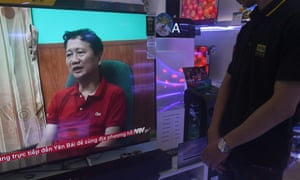 A store employee (R) watches a screen showing Trinh Xuan Thanh speaking in a clip aired by Vietnam's state television VTV, in Hanoi