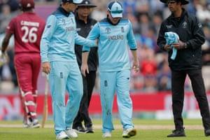 Joe Root (left) checks on Eoin Morgan after England's ODI captain suffers an injury.
