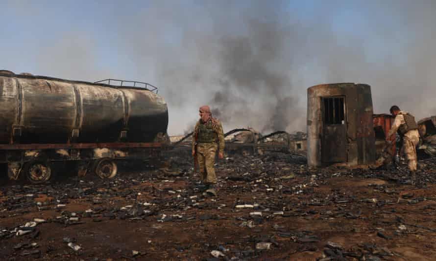 Afghan security personnel walk amidst wreckage of tankers at Islam Qala dry port in Herat province