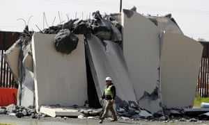 A worker passes a partially-demolished border wall prototype during demolition at the border between Tijuana, Mexico, and San Diego on 27 February 2019.
