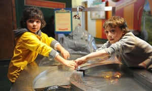 Two boys in the discovery centre, playing with water.