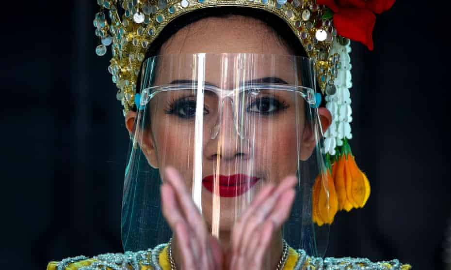 A dancer wearing a protective face shield performs at a temple in Bangkok