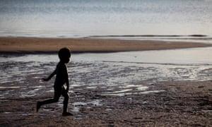 Young Aboriginal boy running on beach at Nyinykay Homeland
