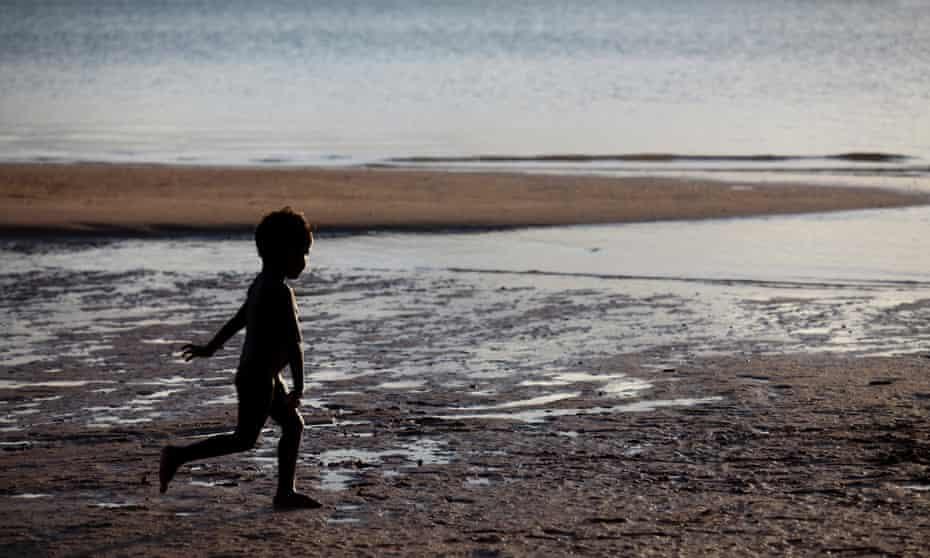 Aboriginal boy running on beach at Nyinykay Homeland.
