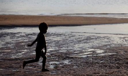 Young Aboriginal boy running on beach