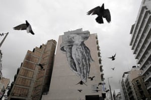 Pigeons fly over a building covered with graffiti in central Athens, Greece, 24 February 2015.