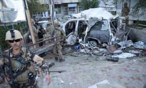 Afghan security forces and British soldiers inspect the site of a suicide attack in the heart of Kabul, Afghanistan.