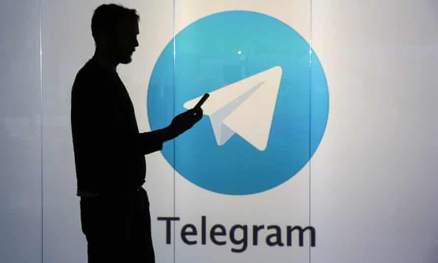 A man is seen as a silhouette as he checks a mobile device whilst standing against an illuminated wall bearing Telegram's logo