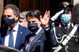 The Italian prime minister, Giuseppe Conte, centre, wears a silky black mask as he leaves the Senate in Rome after an announcement on phase two of the coronavirus lockdown