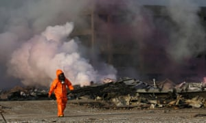 A firefighter works at the explosion site in Tianjin.