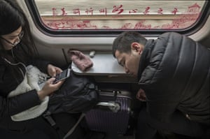 A man sleeps on a train. Most of the travellers are migrant workers and students who return home often from cities back to the countryside