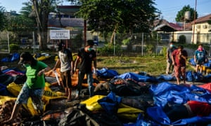 Relatives look for tsunami and earthquake victims in body bags at a police station in Palu