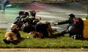 Protesters fall to the ground to take cover after shots were fired