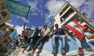Supporters of Saad Hariri wave the Lebanese flag alongside the Saudi and Future Movement flags as they gather at his home in Beirut on Wednesday