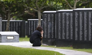 A woman prays in front of a monument to the Battle of Okinawa.