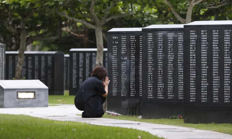 A woman prays in front of a monument to the Battle of Okinawa