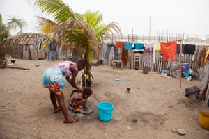 Former street child Mary Nortey helps Meghan take a bath under the water spicket at Streetwise, a nonprofit that helps street children, in Accra, Ghana