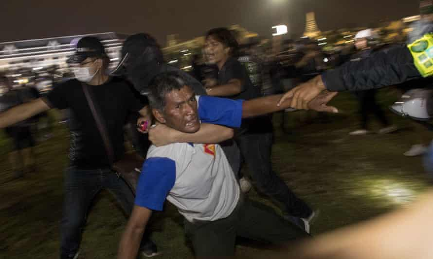 Pro-democracy protesters help carry an injured man