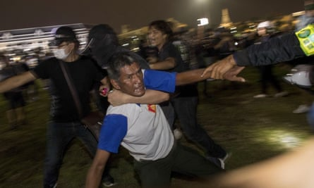 A pro-democracy protester helps an injured man