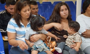 Mothers and children wait to be assisted by volunteers at a humanitarian center in the border town of McAllen, Texas on Friday.
