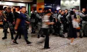 Riot police wait at a Mass Transit Railway (MTR) station as commuters walk past in Hong Kong