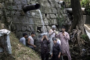 Islamabad, Pakistan Locals cool themselves off under a water pipe as the country experiences a heatwave