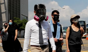 Anti-government office workers wearing masks attend a lunch time protest, after local media reported on an expected ban on face masks under emergency law.