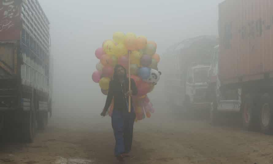 A Pakistani vendor carries balloons down a Lahore street amid heavy smog.