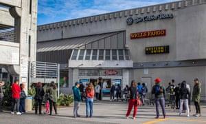 People wait in line to buy food at a grocery store in Koreatown, Los Angeles, earlier this week.