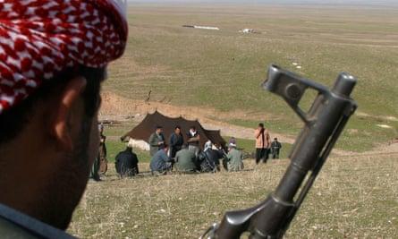 A Kurdish fighter guards Iraqi refugees at a camp in Erbil