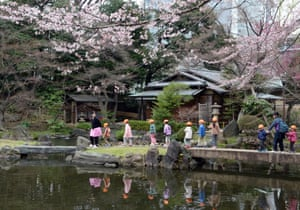 Visitors walk in a park in Tokyo