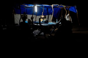 Staff members from Unicef and the World Food Programme work late into the night, sorting registration tokens by the light of a solar powered lamp