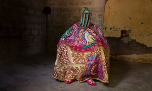 A member of an Egungun masquerade group, his identity obscured under his ornate costume in Ouidah, Benin