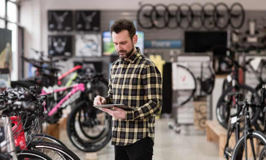 Small business owner using digital tablet in a cycle store. Image shot 2018. Exact date unknown.MNMW42 Small business owner using digital tablet in a cycle store. Image shot 2018. Exact date unknown.