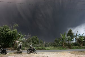 Resident rides a motorcycle as Mount Sinabung during an eruption in Karo, Indonesia